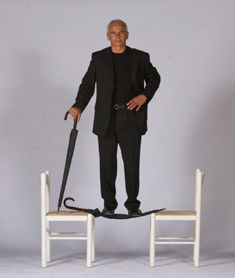 Man stands on the Unbreakable Umbrella suspended between two chairs